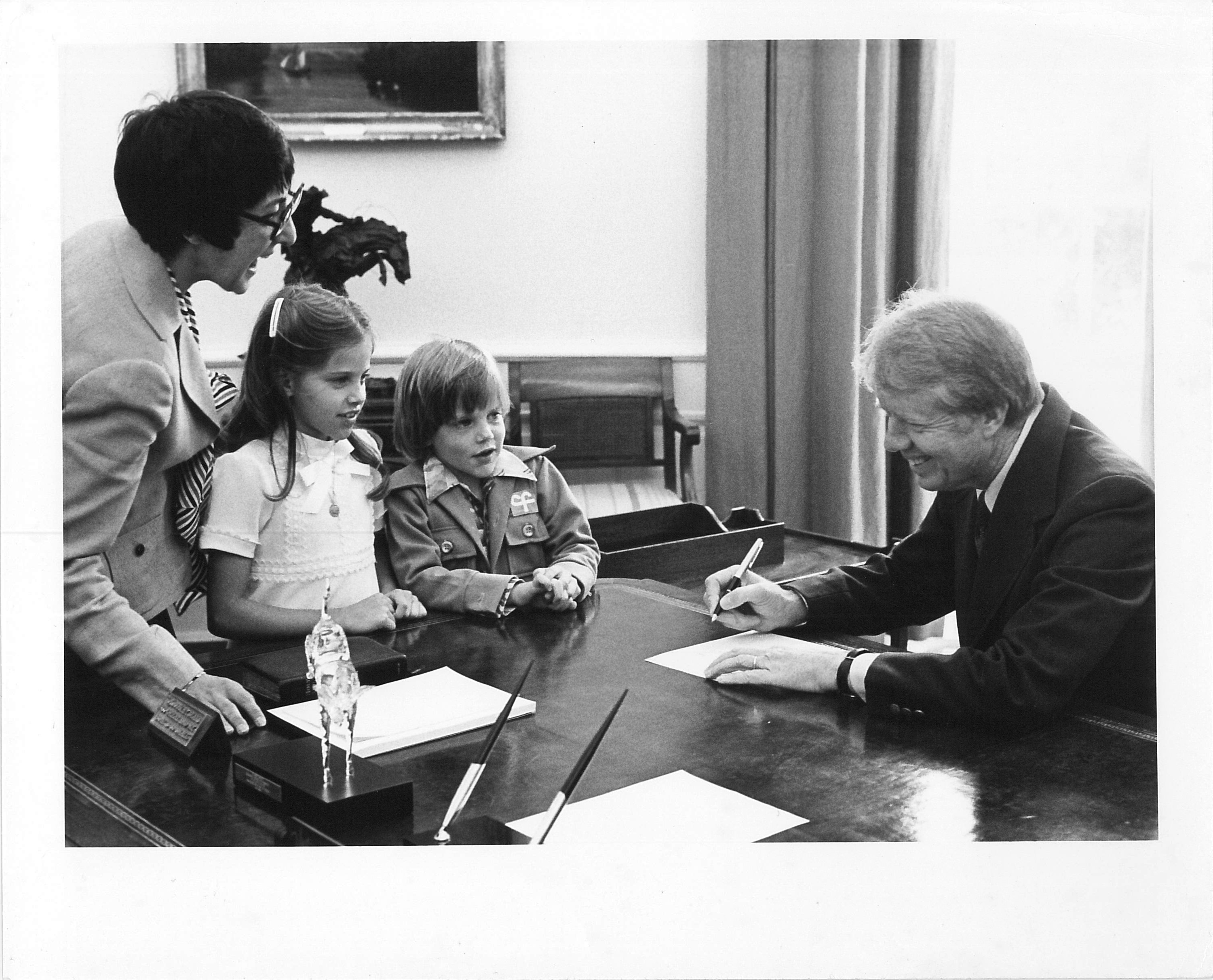 Photograph of Midge Costanza and Jimmy Carter with children in the Oval Office