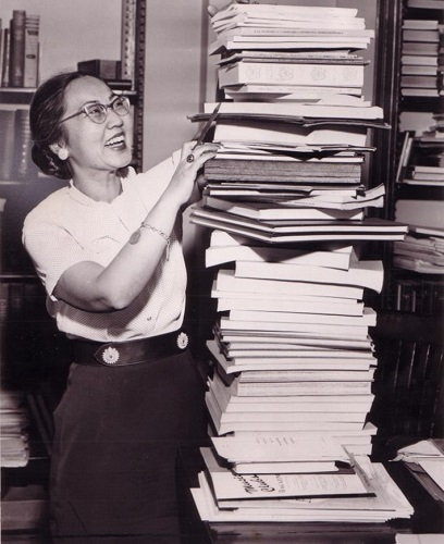 Ruth Watanabe standing near a tall stack of publications