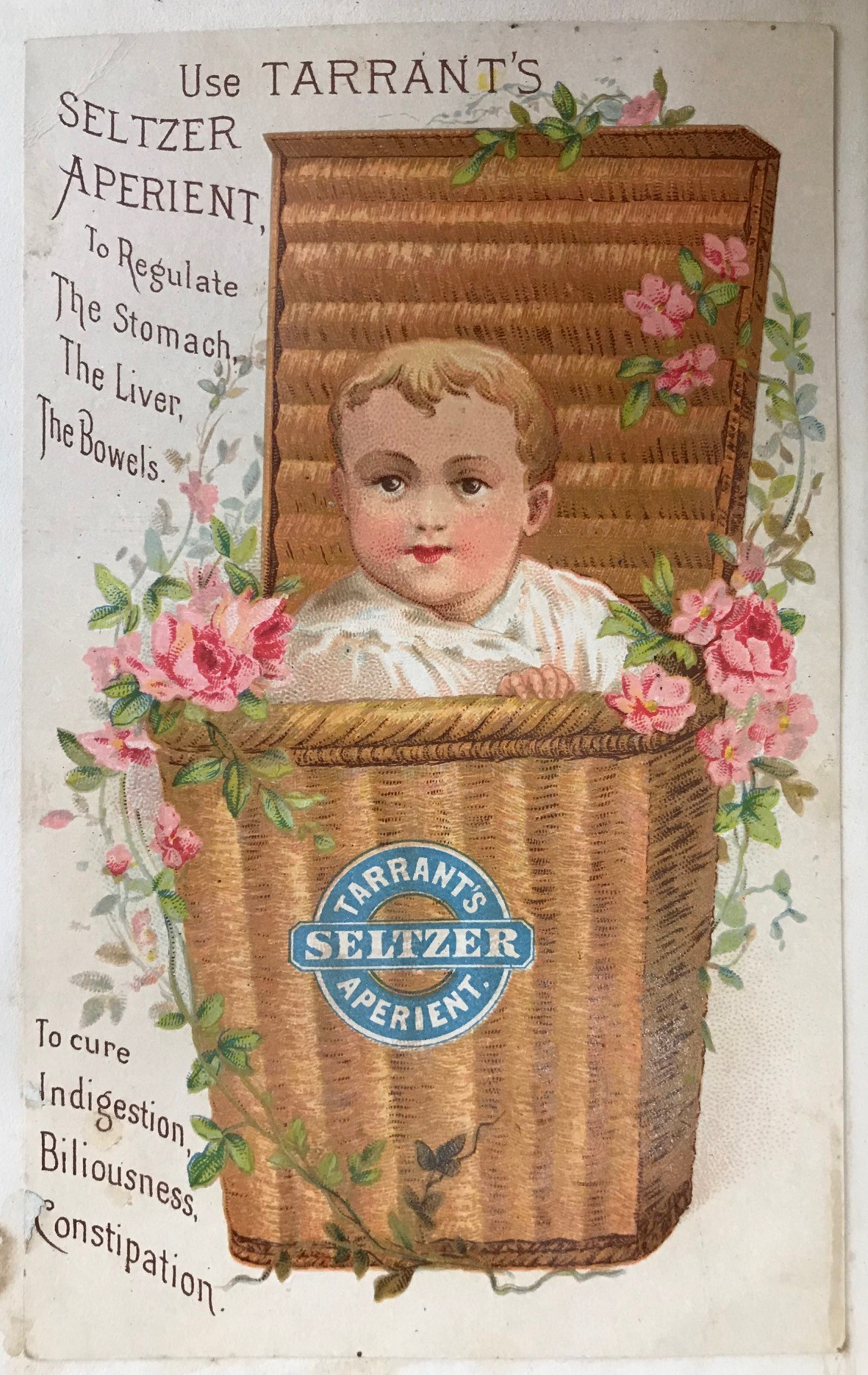 Trade card with a baby in a floral basket advertising Tarrant's Seltzer Aperient, 1880s