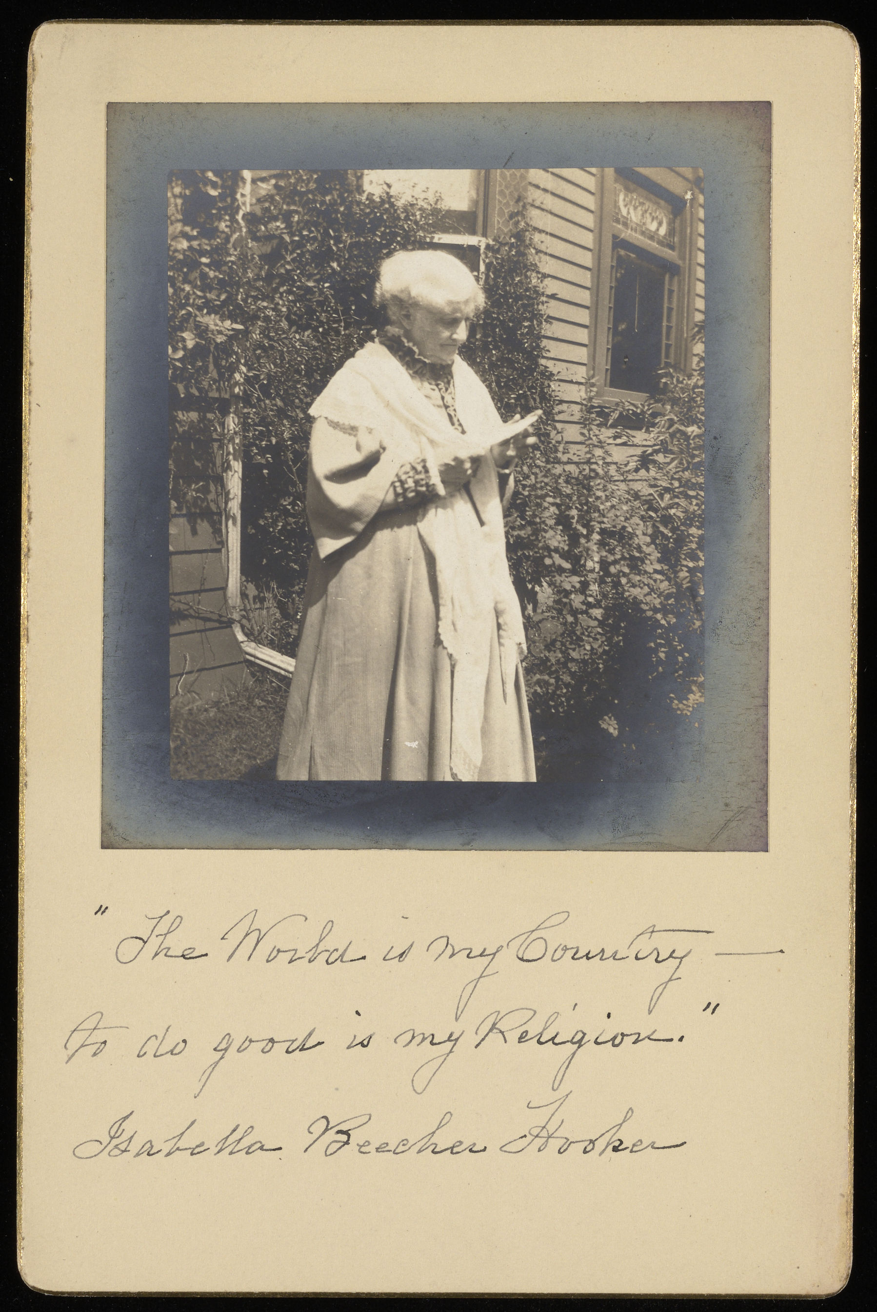 "image of Isabella Beecher Hooker standing outside a house, looking at a letter in her hands. Handwritten inscription at the bottom: ""The World is my Country- To do good is my religion. Isabella Beecher Hooker"""