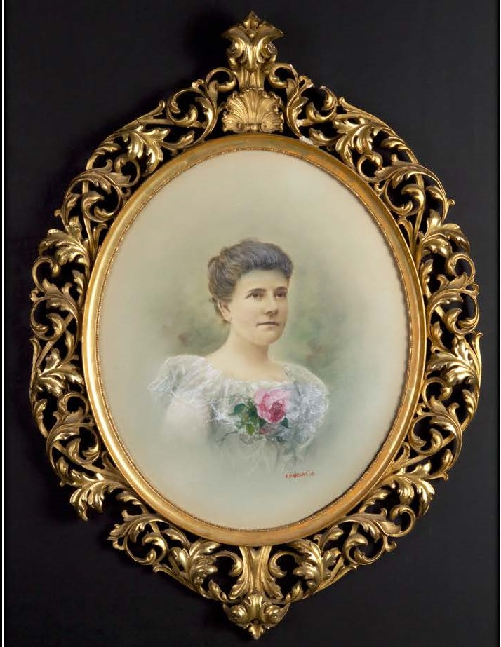 Oval gilt-framed portrait of a white woman, brown hair upswept, wearing a lacy white dress with a pink rose pinned to the front
