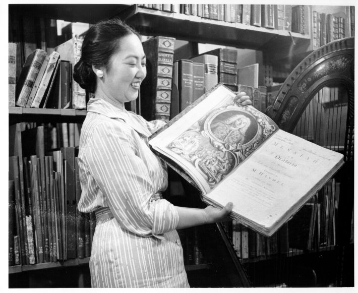 Ruth Watanabe holds a book open in the library stacks